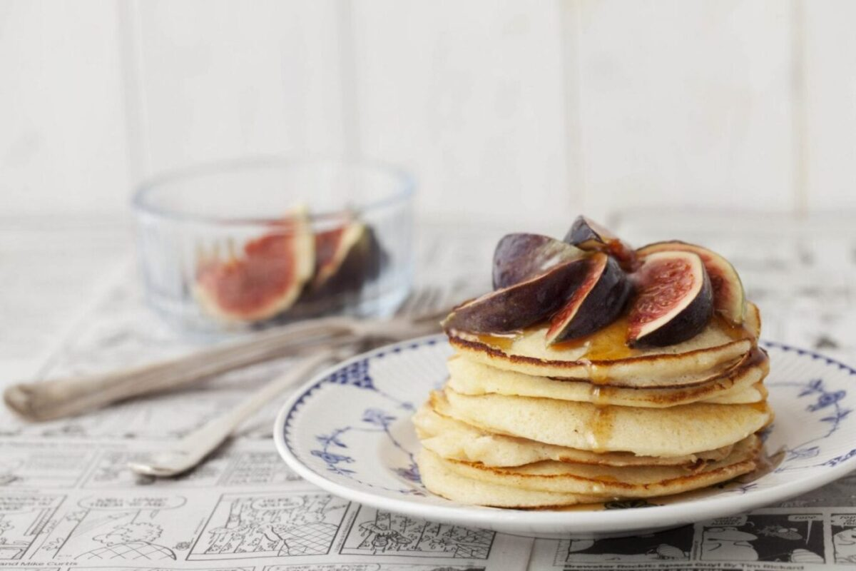 Horizontal view of Pancakes stacked up with figs and syrup