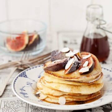 A stack of ricotta & almond pancakes serves with figs, almonds and syrup and duated with icing sugar. Served on a blue & white plat which is sitting on a black & white comic strip