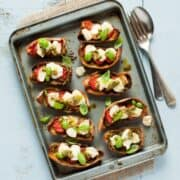 Ten loaded Potato Skins with Pesto and Goats Cheese on a baking sheet which is on a piece of cloth with serving utensils next to it.