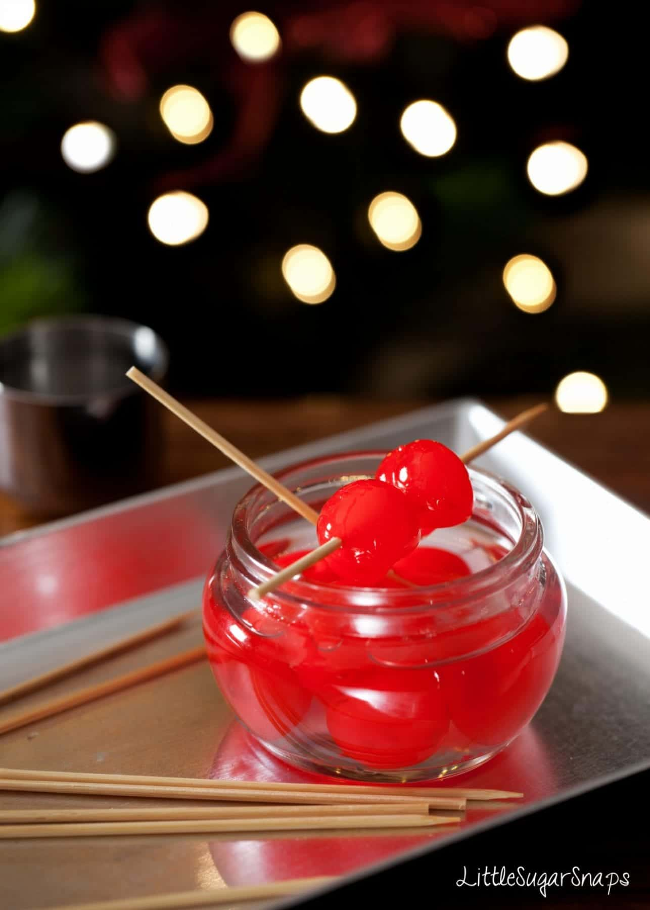 A pot of maraschino cocktail cherries on a tray with wooden cocktail sticks