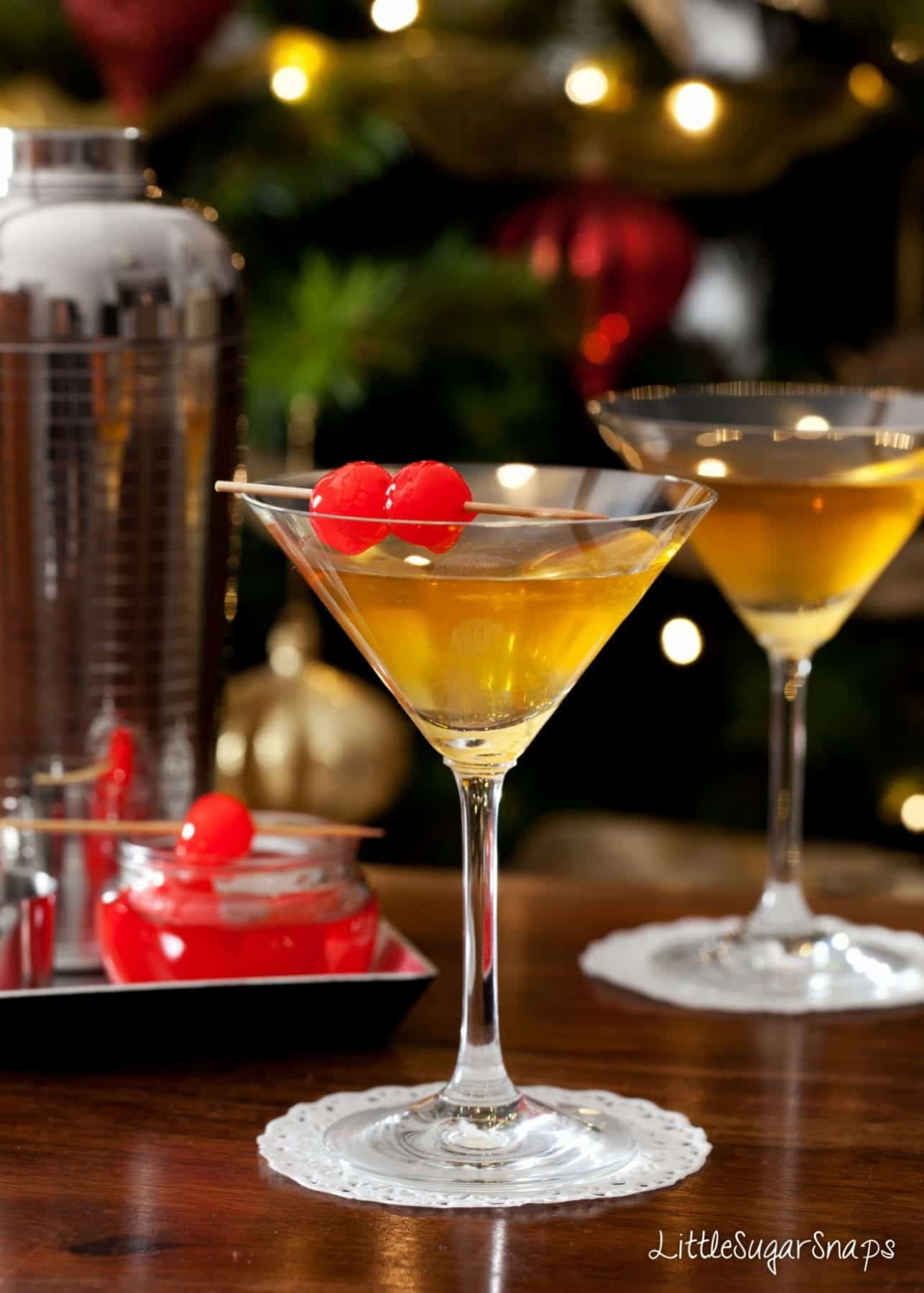 Cocktails served with Maraschino cherries in front of a Christmas tree