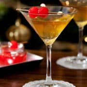 A martini served with maraschino cherries in front of a Christmas tree