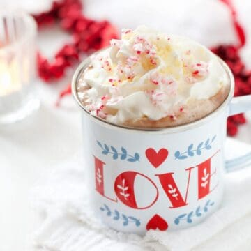 An enamel mug (with the word love on it) of hot chocolate with cream, crushed candy cane pieces and popping candy. Christmas decorations in the background