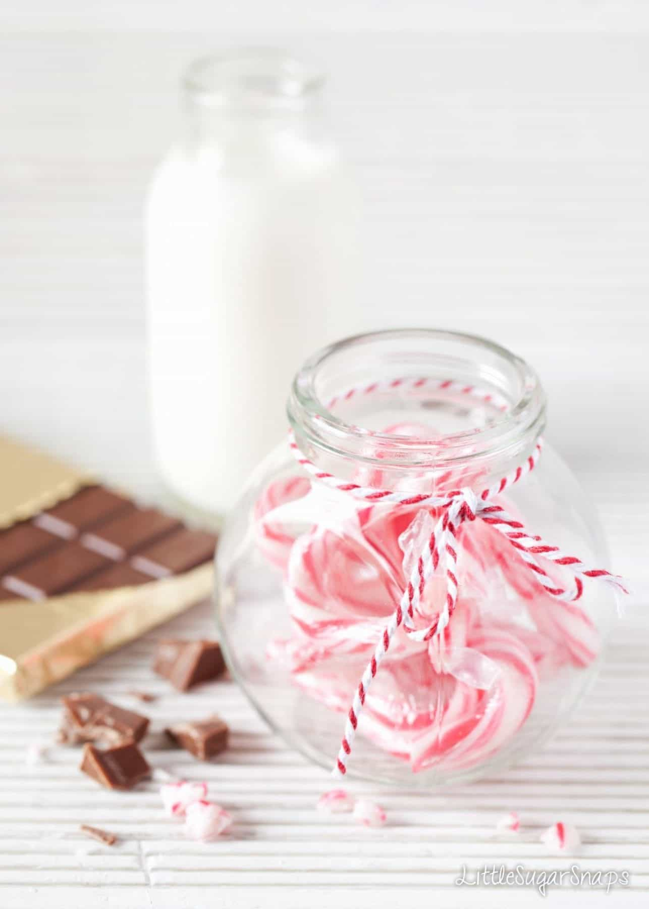 A jar of candy canes, a bottle of milk and a bar of chocolate