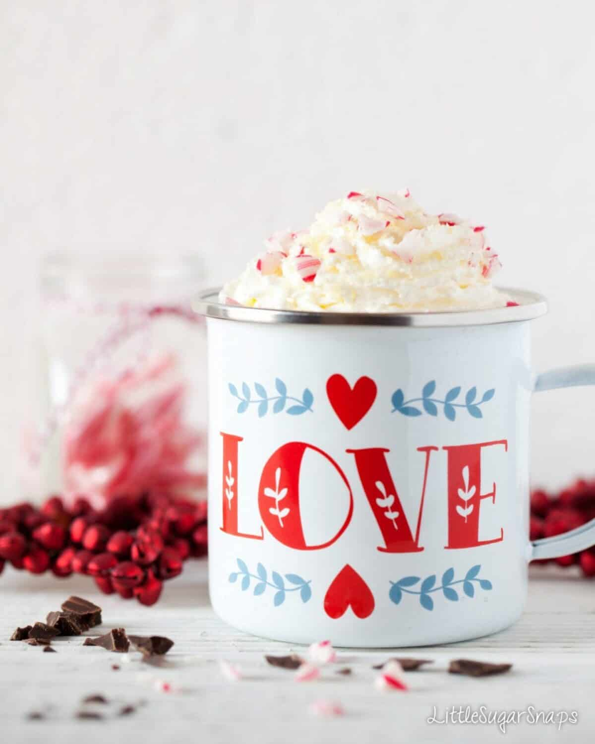 An enamel mug of hot chocolate with cream and candy cane pieces