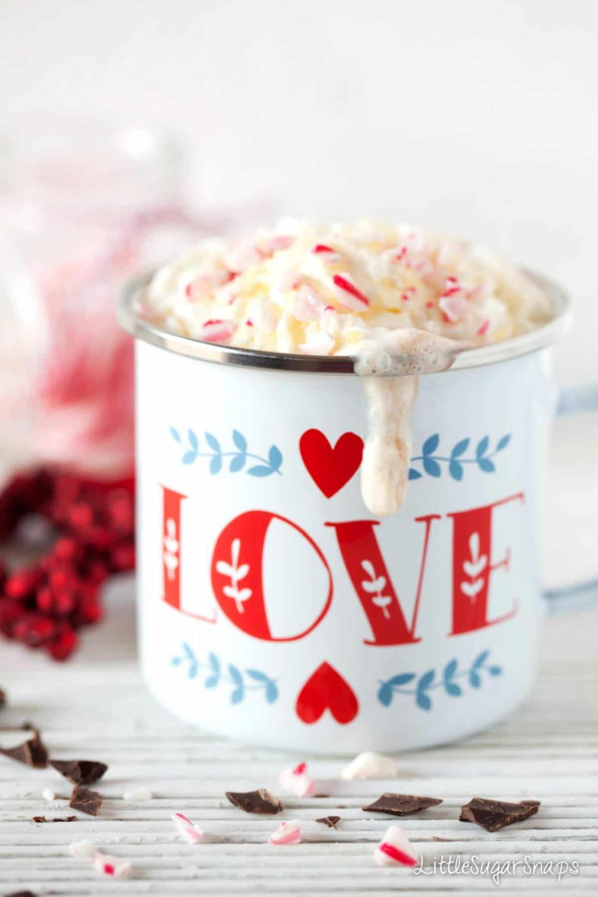 Cream running down the side of a heart-design enamel mug
