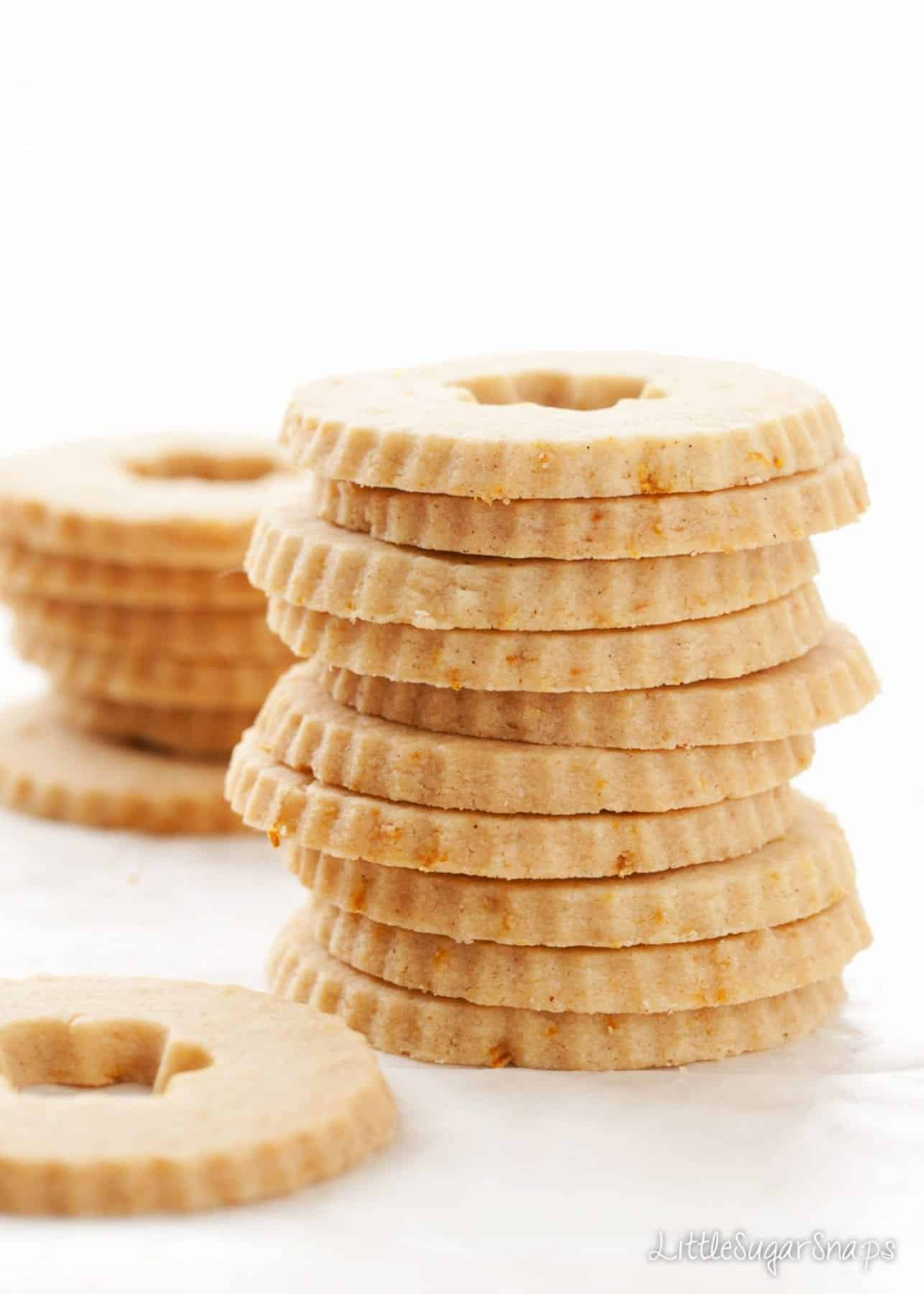 A stack of fluted edge circular biscuits holes in the centres