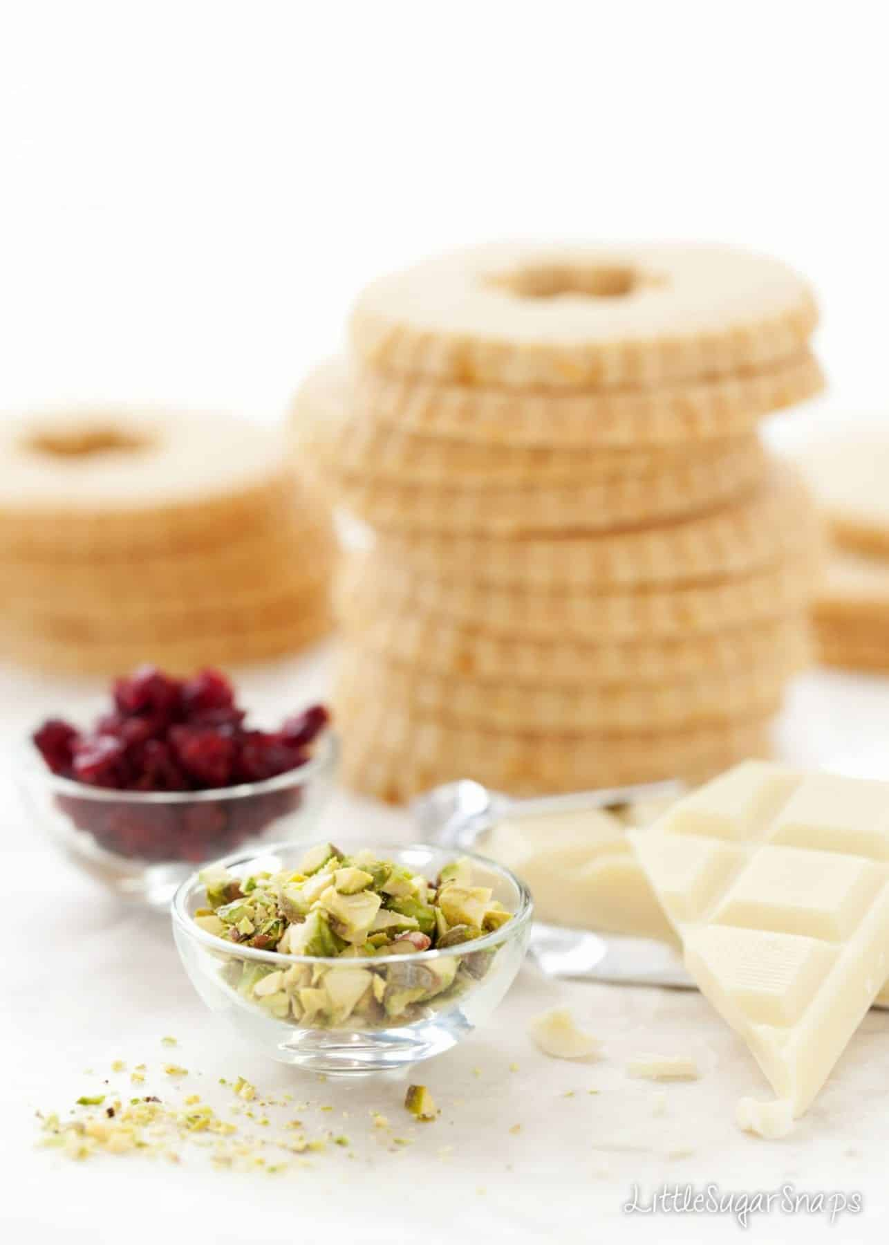 Pistachios, cranberries and white chocolate with a stack of cookies behind