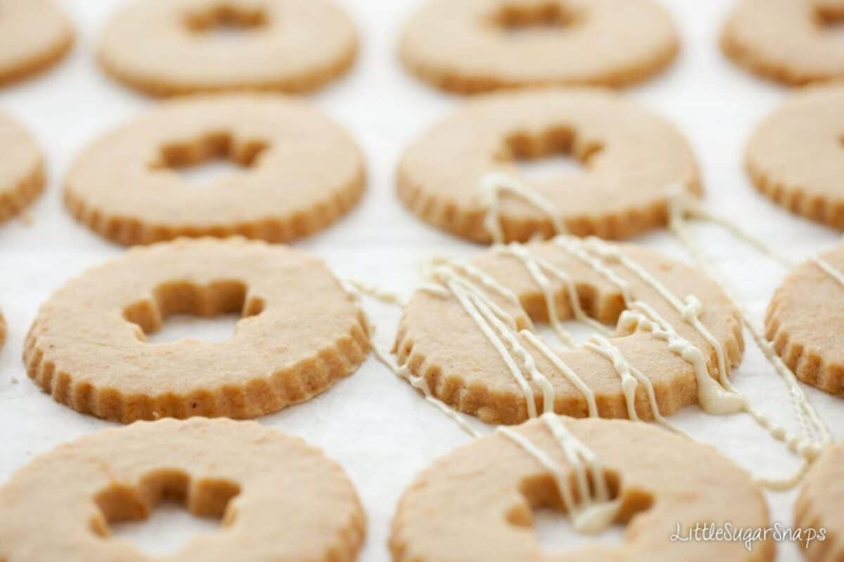 Biscuits being drizzled with melted white chocolate