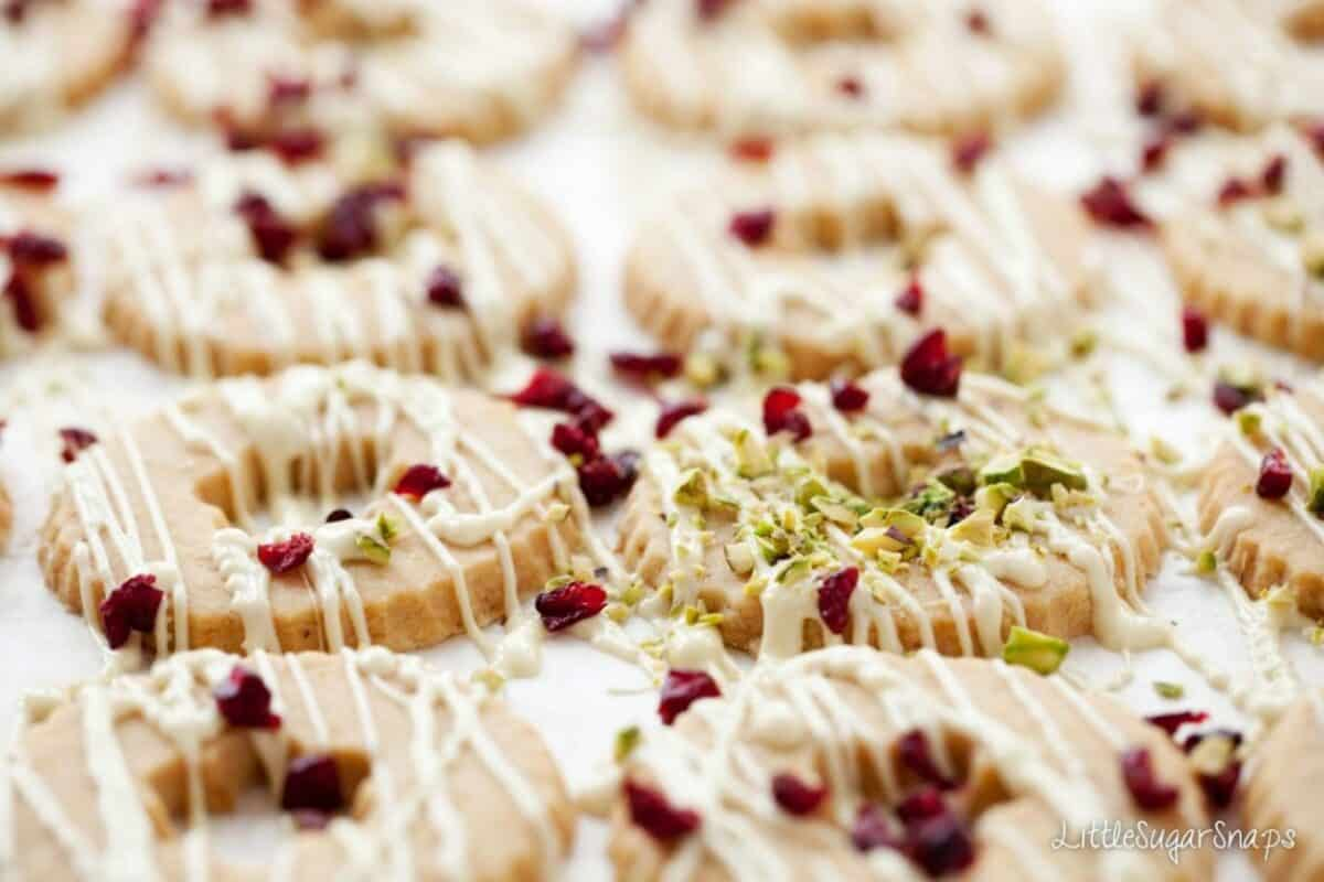 Christmas wreath cookies being decorated with white chocolate, pistachios and cranberries