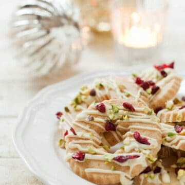 Christmas wreath biscuits topped with white chocolate, cranberries and pistachio nuts. Served on a white plate with baubles in the background