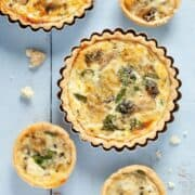 Overhead view of Blue Cheese, watercress and artichoke tarts. A large tart in in it's baking tin, smaller tarts on on the worktop