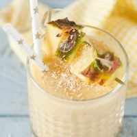 Pineapple coconut cold busting smoothie with chunks of fresh pineapple, dessicated coconut and paper straws garnishing this yellow drink