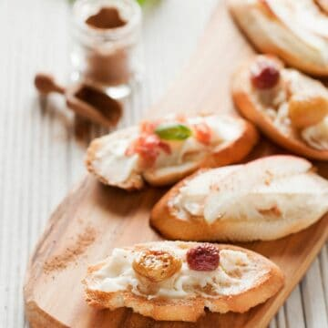 A platter of mixed taleggio crostini topped with roasted grapes, apple and parma ham