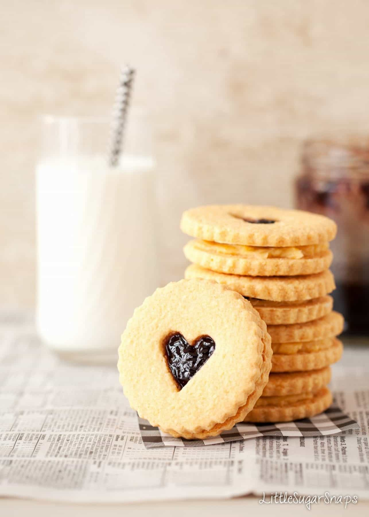 A stack of jam and custard creams biscuits with a love heart cut out to reveal the jammy centre
