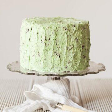 A cake covered in green icng with chocolate pieces in it to give the look of mint choc chip. They cake is on a glass stand with a cloth wrapped around it