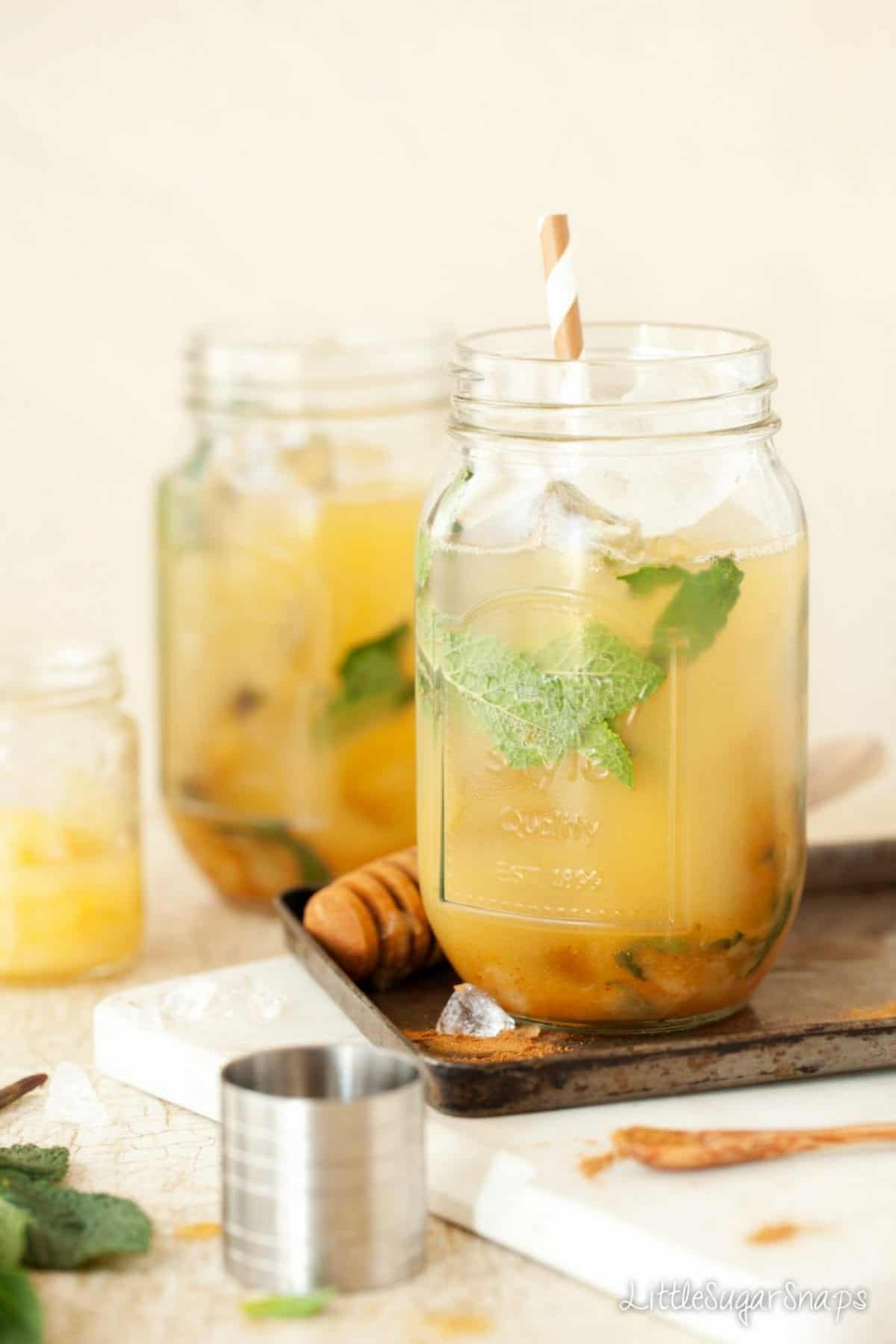 A blend of bourbon, pear, pineapple, mint and cinnamon drink in a jam jar with a cocktail jigger in shot