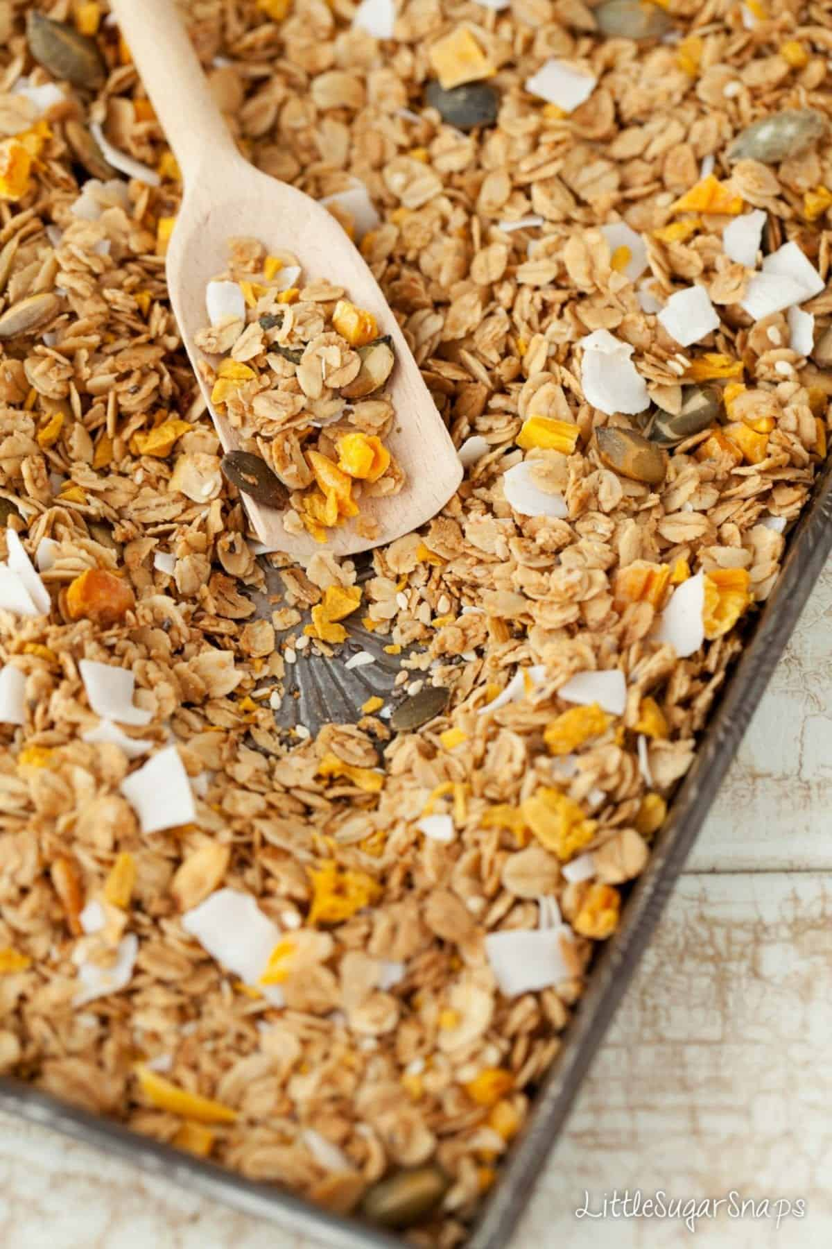 freshly baked granola on a baking tin