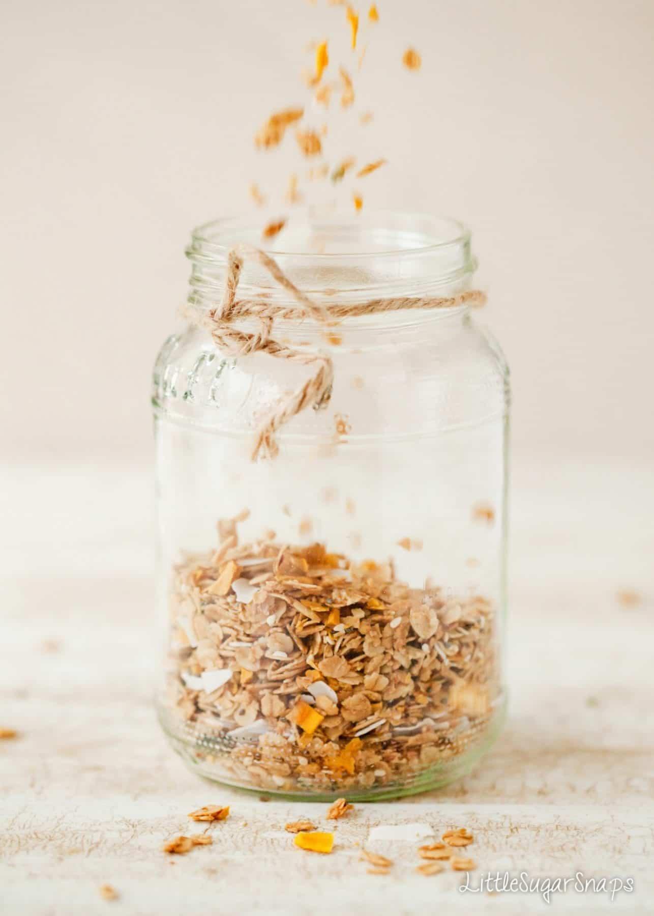 Homemade Granola being poured into a glass jar for storage