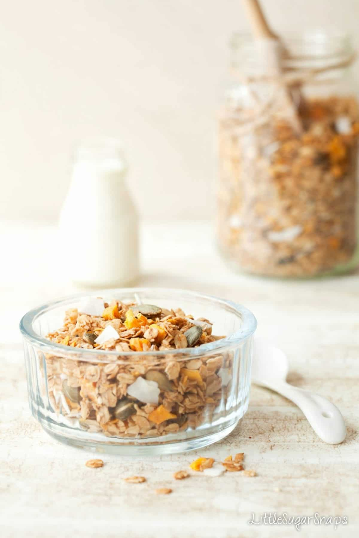 Granola in a bowl with dried mango, coconut and pumpkin seeds