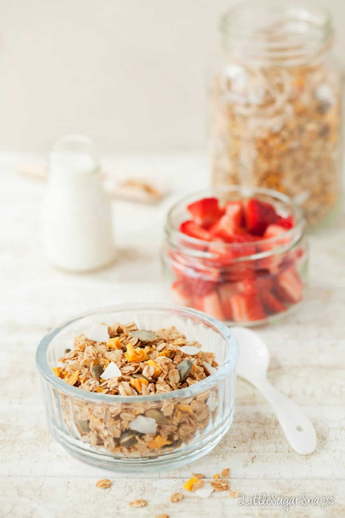 Granola with dried mango, coconut and pumpkin seeds and fresh strawberries