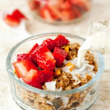Milk being poured into a bowl of coconut and mango granola topped with chopped strawberries