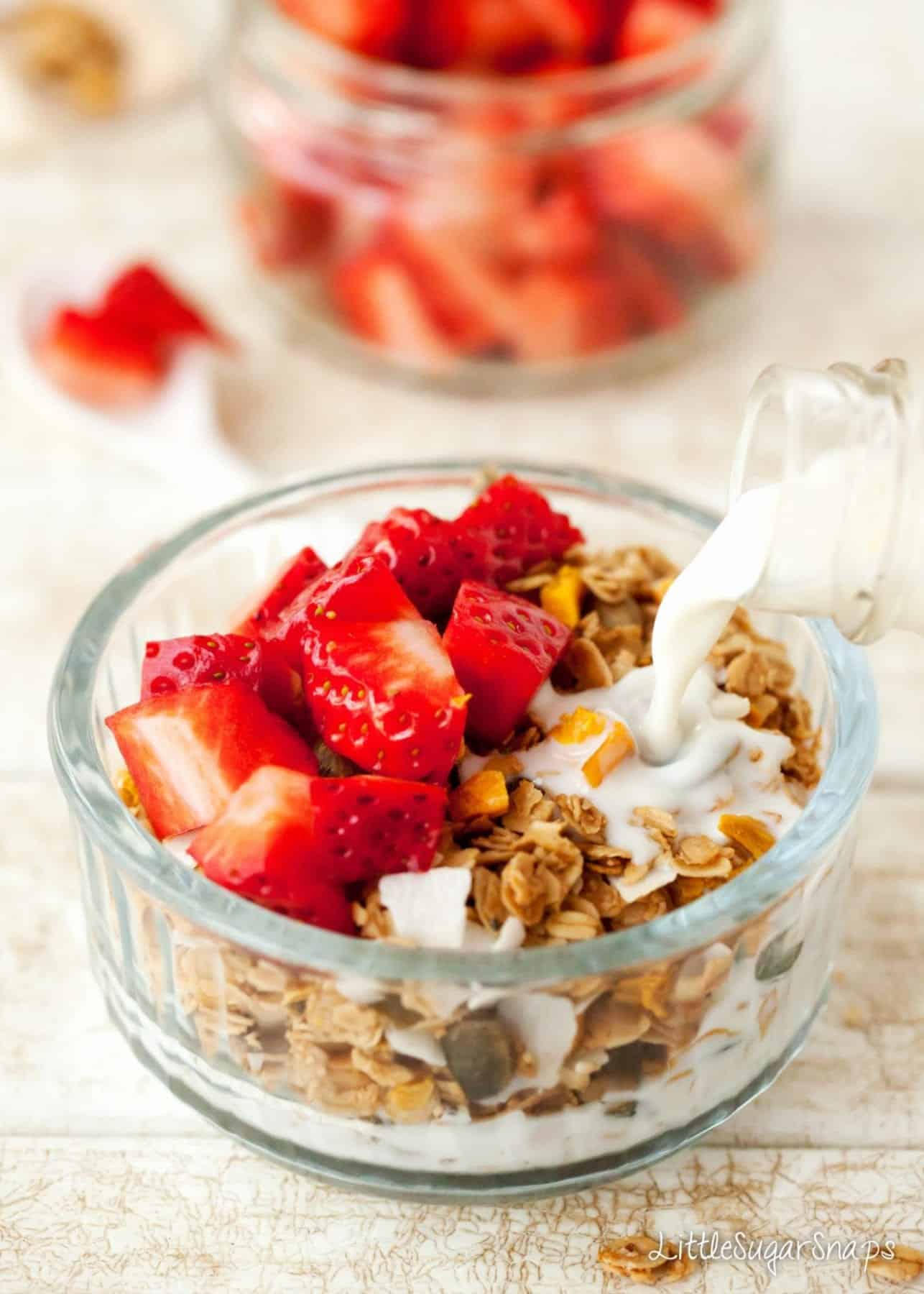Milk being poured onto a bowl of granola with strawberries on top
