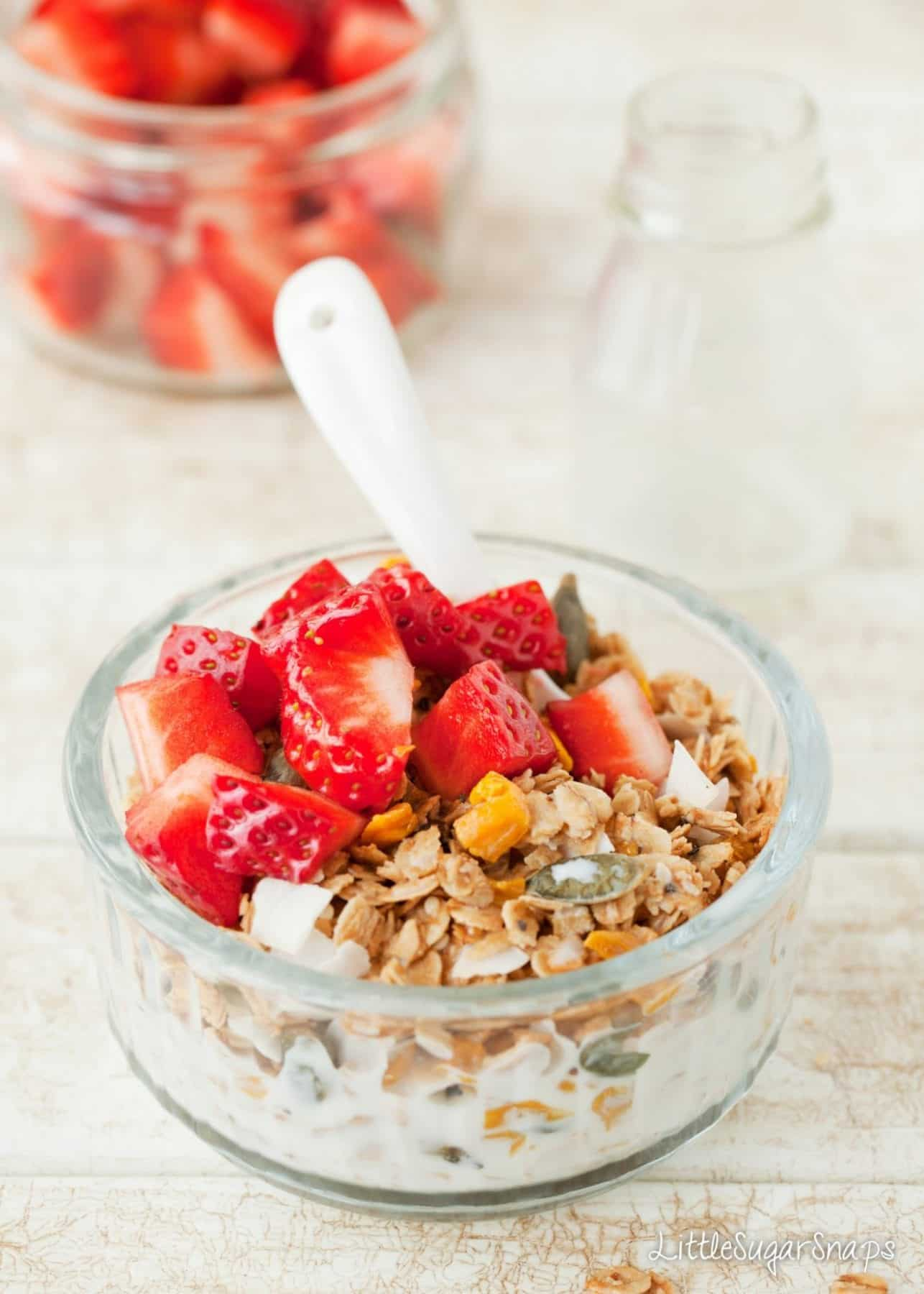 Bowl of Coconut Mango Granola topped with milk and strawberries