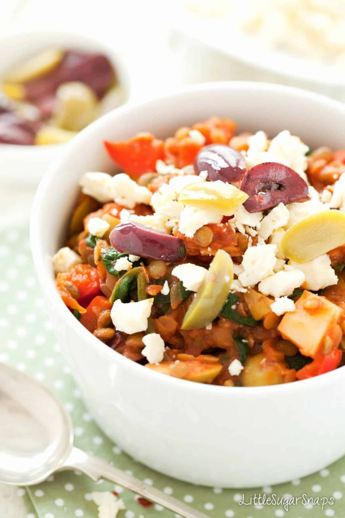 Close up of lentil & olive Stew topped with feta and sliced olives