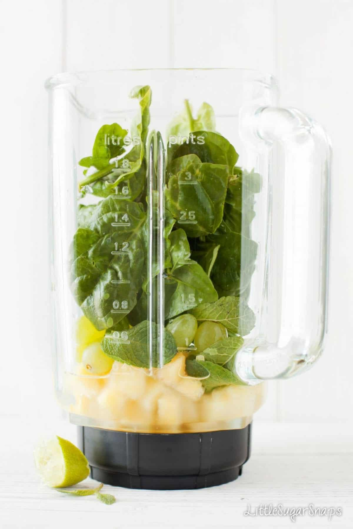 A blender jug filled with smoothie ingredients - mint, pineapple & grapes