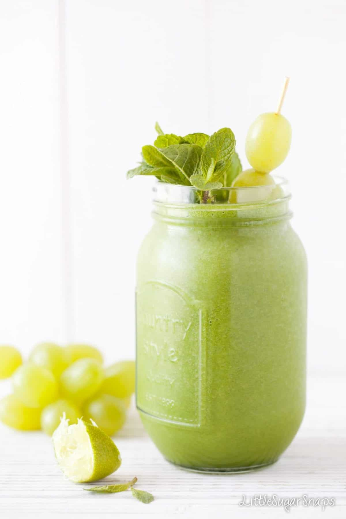A green smoothie topped with grapes and mint