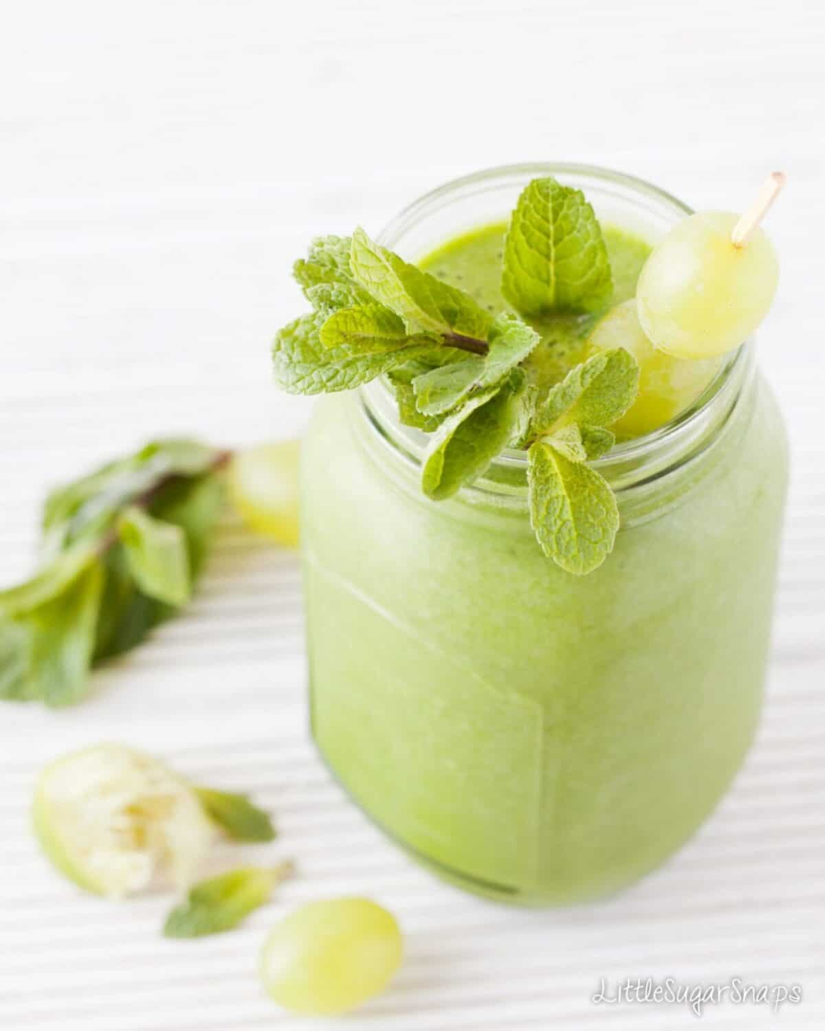 A green grape smoothie topped with grapes and mint