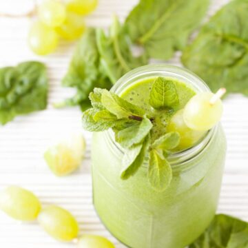 A green smoothie topped with grapes and mint and ingredients surrounding it on the white wooden worktop