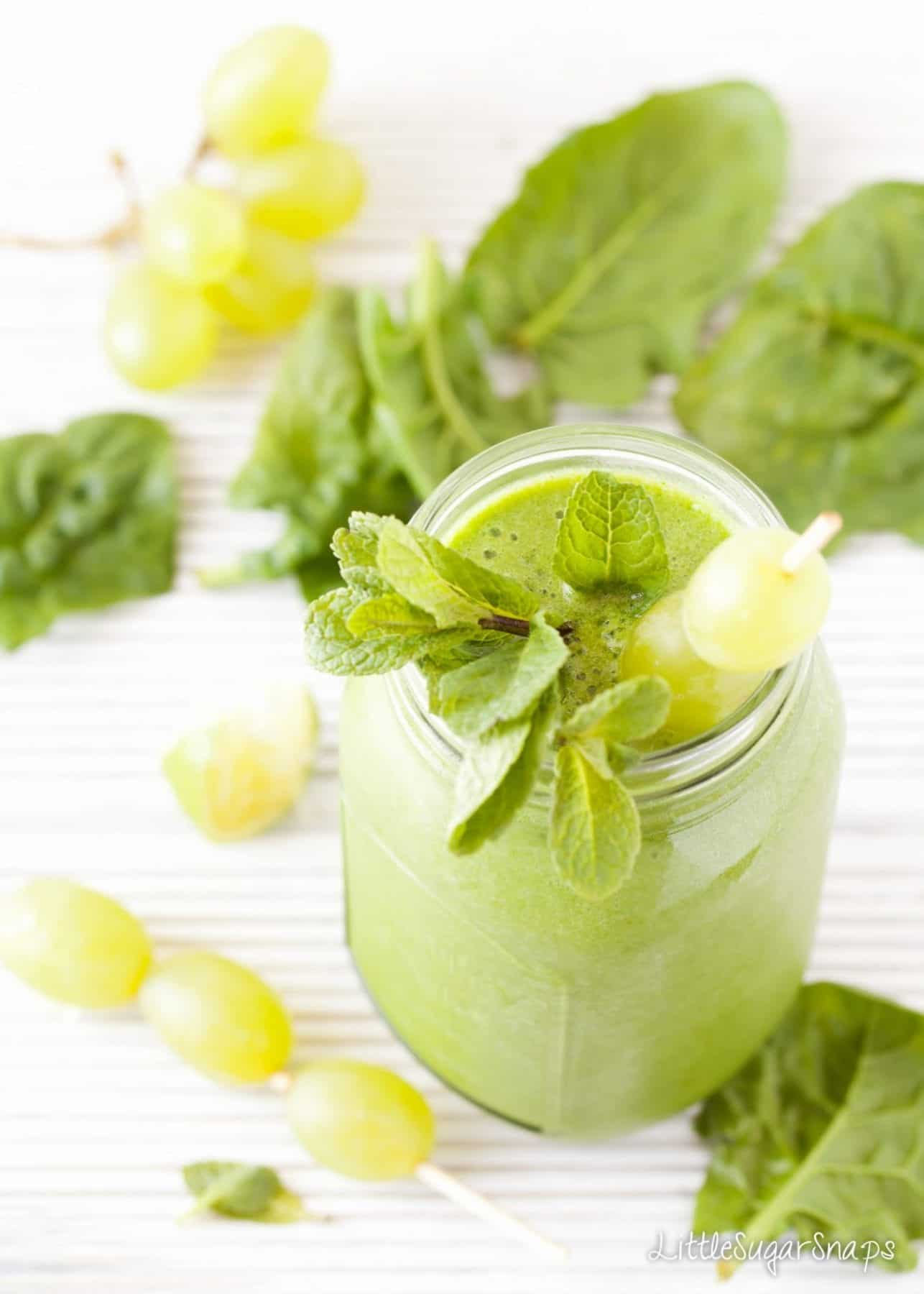 Green grape smoothie in a jam jar with grapes on a skewer and mint