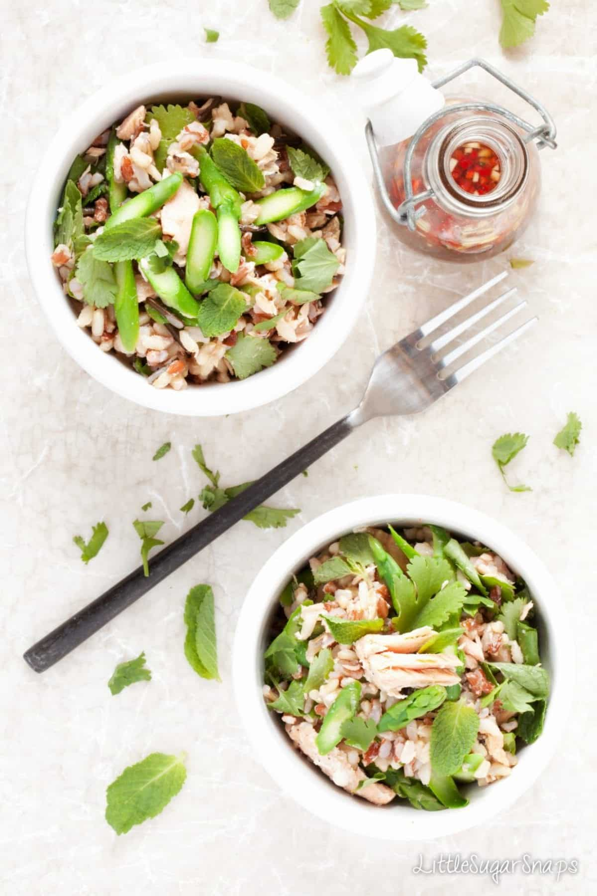 Two salad bowls of rice, salmon, asparagus and green herbs.