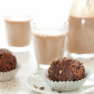 Chocolate nut truffle balls served with chocolate milkshake.The balls have been covered in chocolate strands and the one in focus has been bitten into