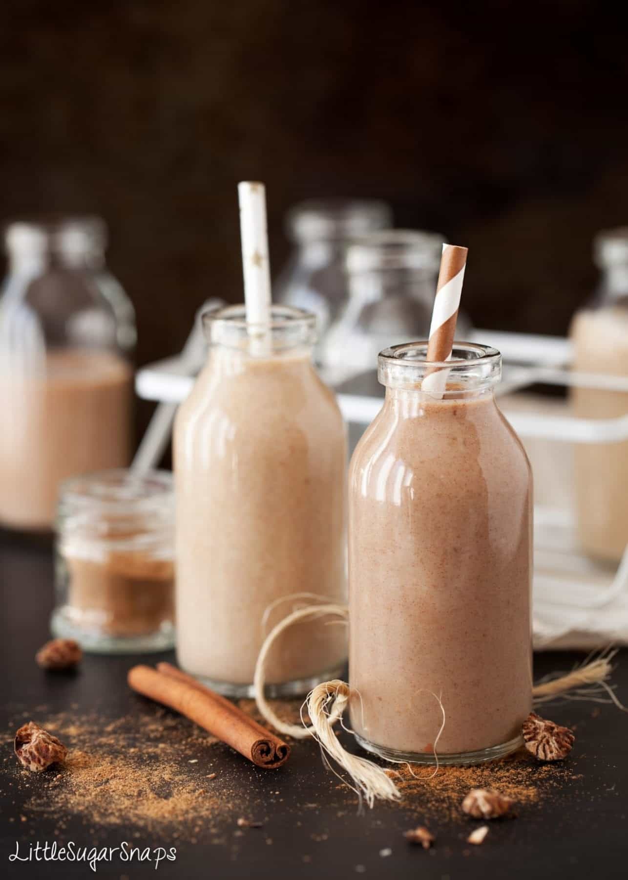 Date milkshake presented in small glass milk bottles on a black worktop. String, cinnamon stick, nutmeg and ground spices on the worktop near the bottles