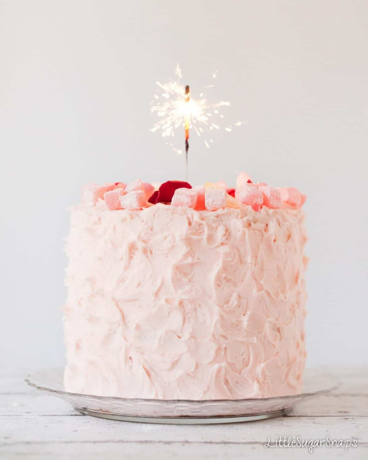 A celebration cake covered in pink frosting and decoated with turkish delight chunks and rose petals with a lit sparkler in the centre
