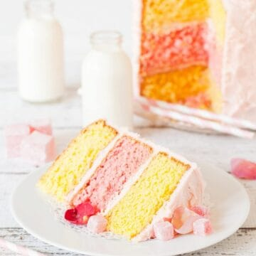 A lemon and rose triple layer cake cut open with a slice on a plate in focus at the front of the shot. Two yellow lemon layers and one pink rose layer are sandwiched together with pink icng and decorated with turkish delight and rose petals