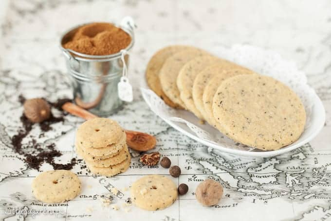 A plate of full size tea flavoured biscuits plus some mini biscuits on a printed parchment next to them. Whole and ground cinnamon and nutmeg in the image.