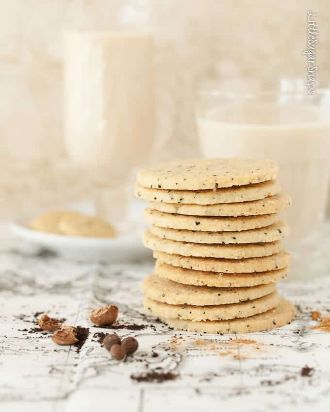A stack of chai shortbread cookies with flecks of black tea in them. On printed parchment with black tea and chai spice mix scattered around. Glasses of masala chai in the background