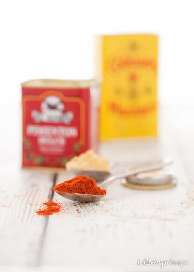 Ingredients - paprika and mustard powder on spoons with their jars behind