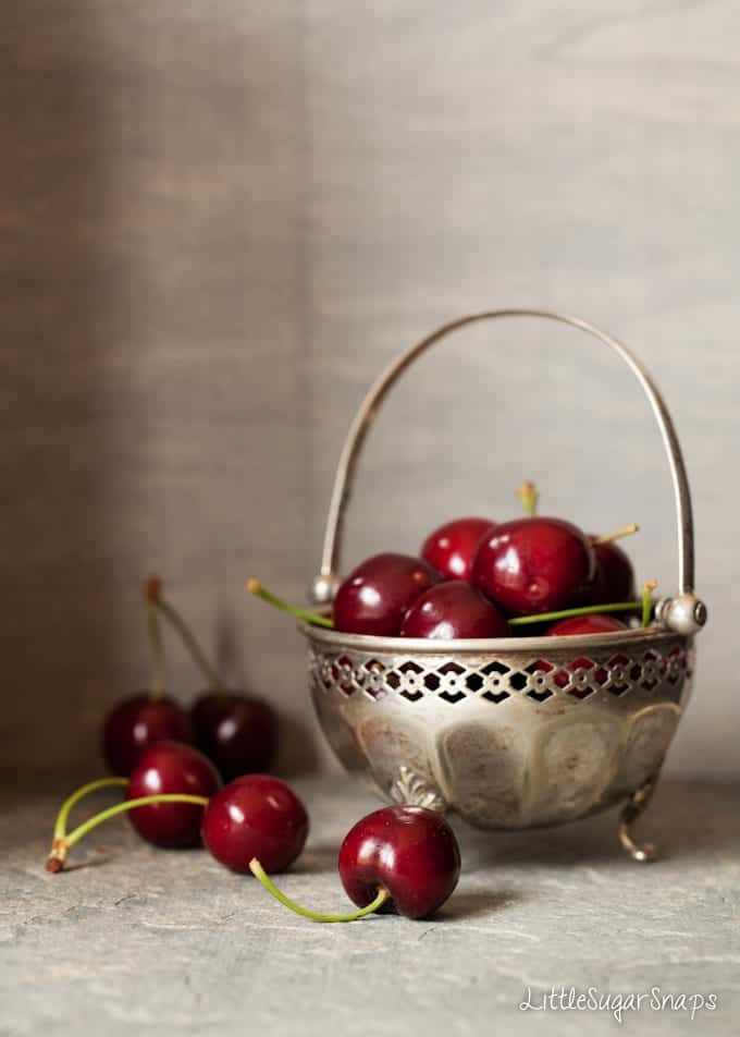 Vintage bowl filled with cherries on a tabletop