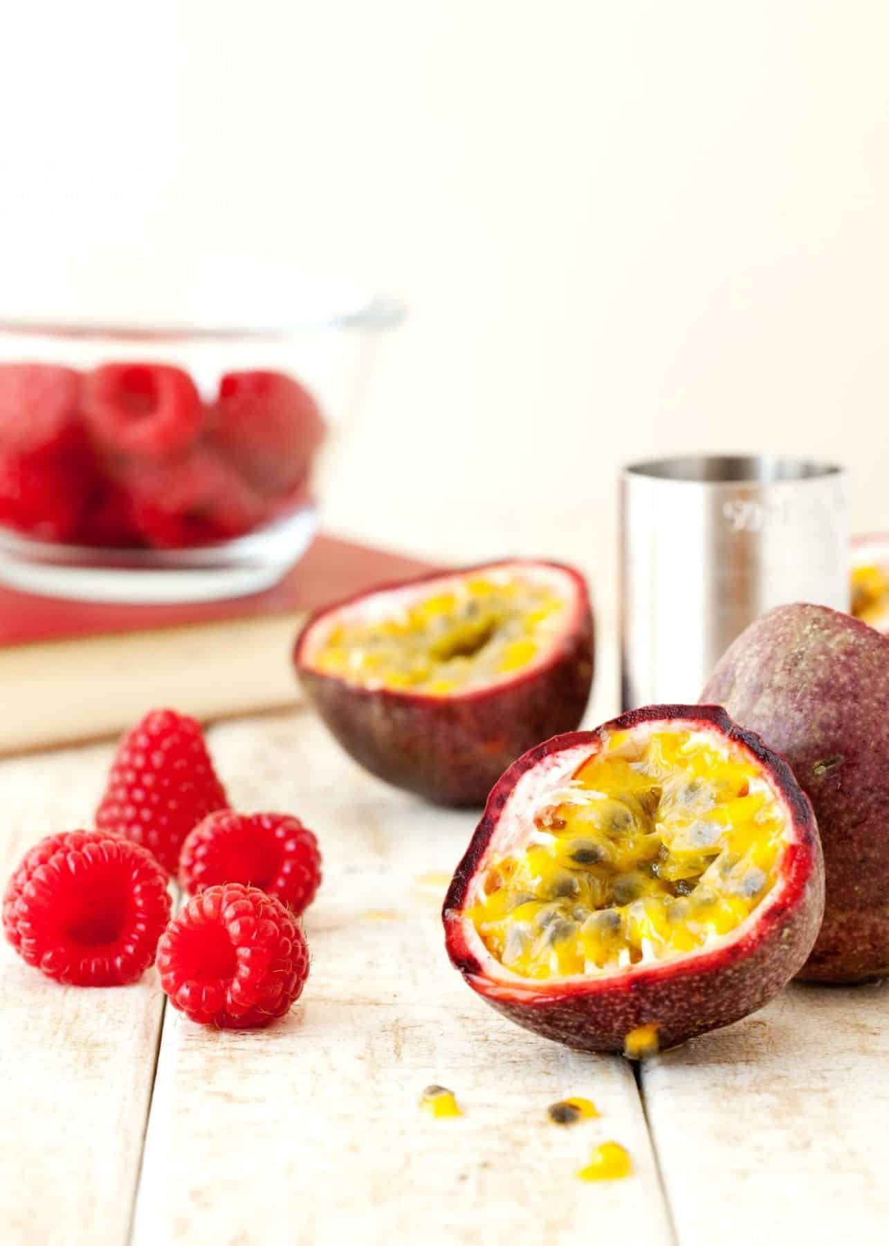 Fresh passionfruit and raspberries on a worktop
