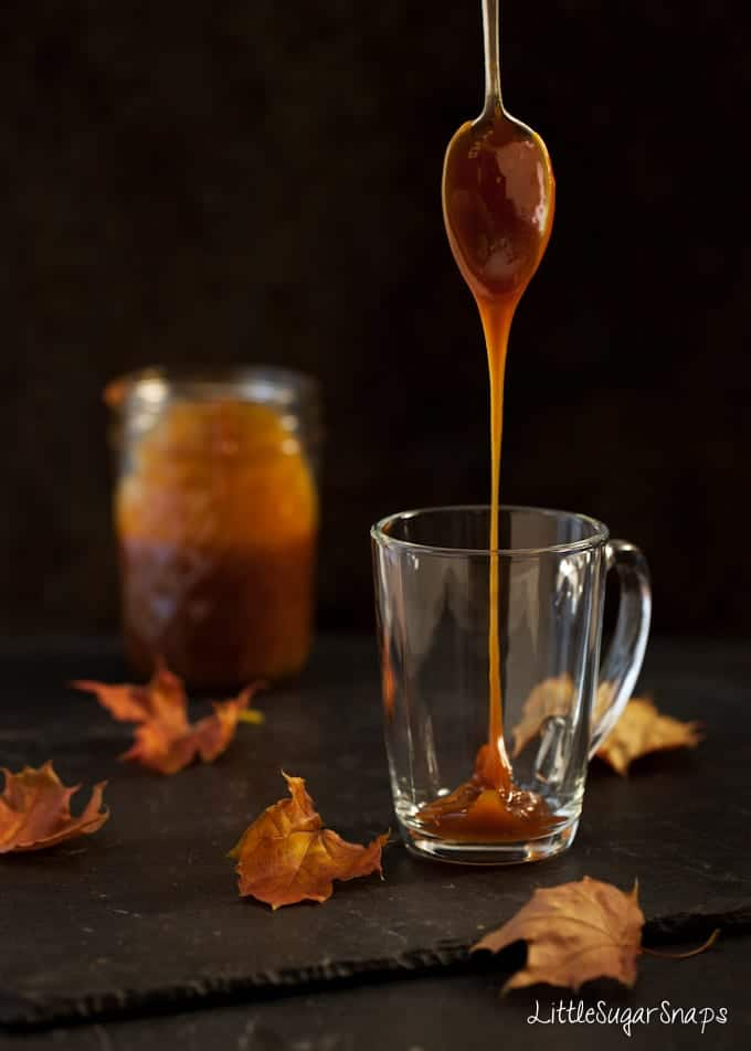 Caramel sauce dripping from a spoon into a glass mug.