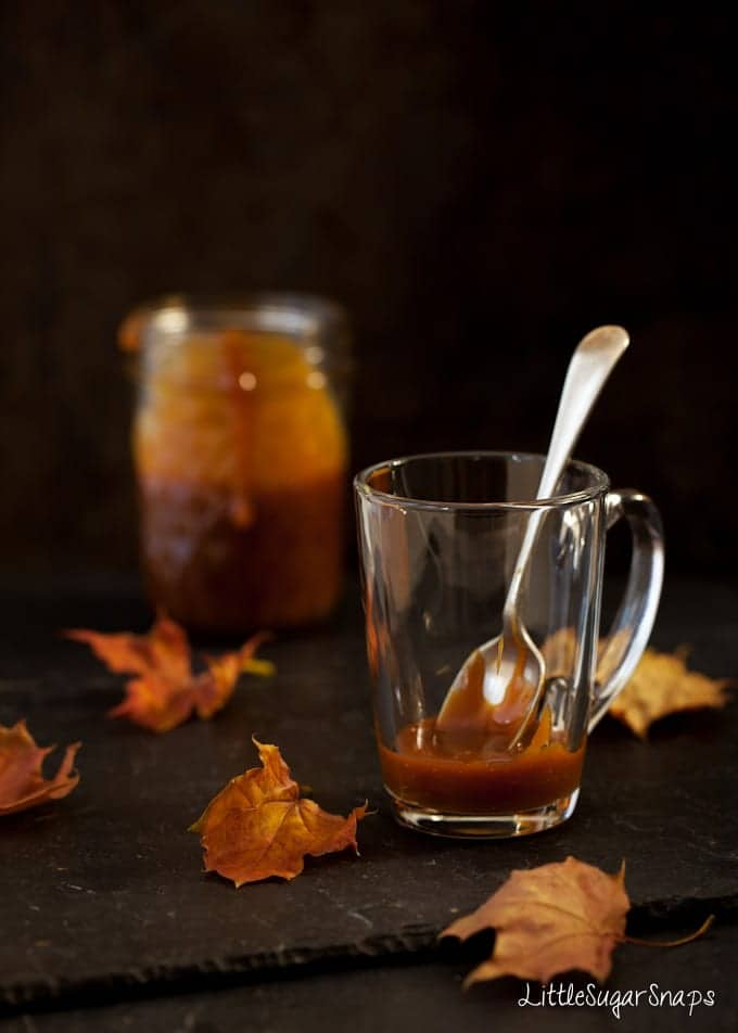 Caramel sauce in a glass mug surrounded by autumn leaves