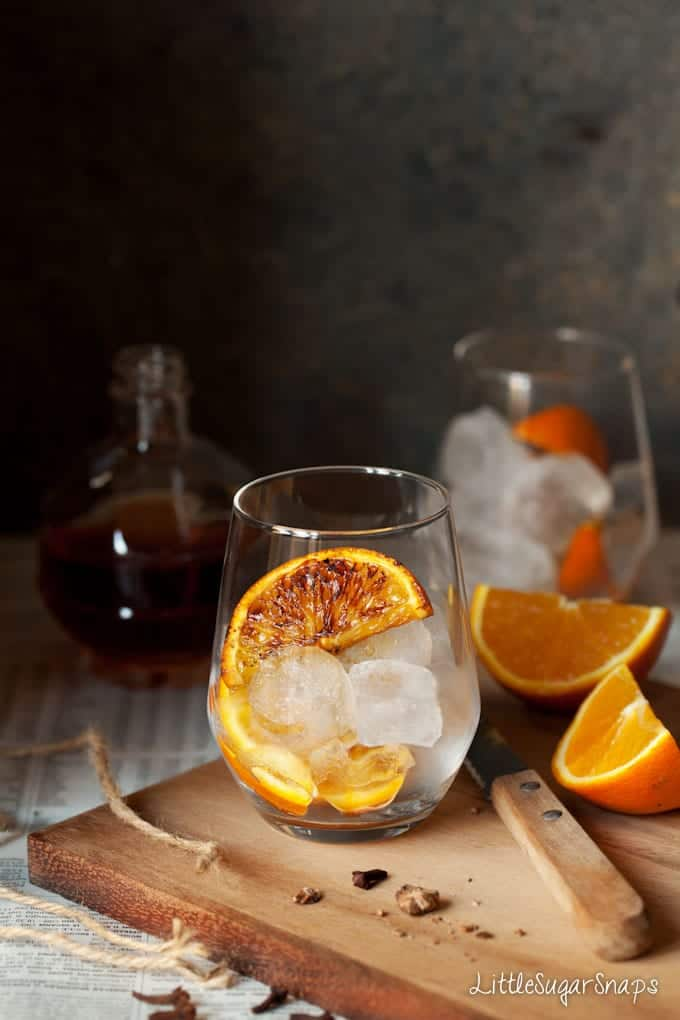 charred orange wedges and ice in a glass
