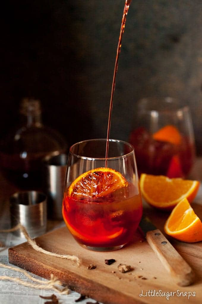 Pouring a spiced negroni into a glass