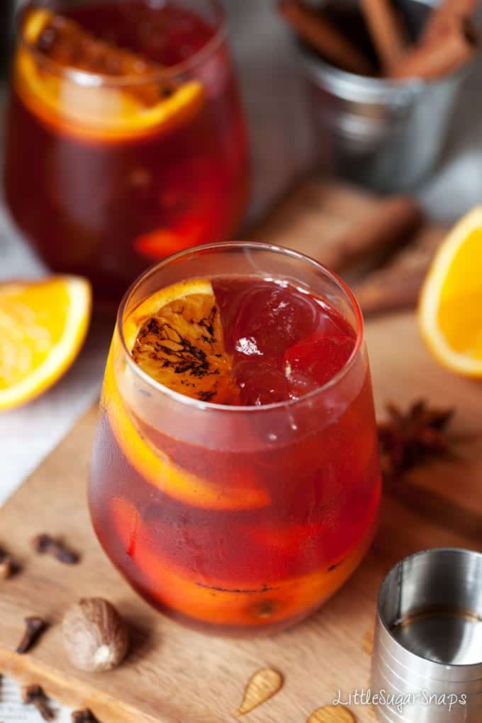 A spiced negroni cocktail garnished with a charred orange wedge