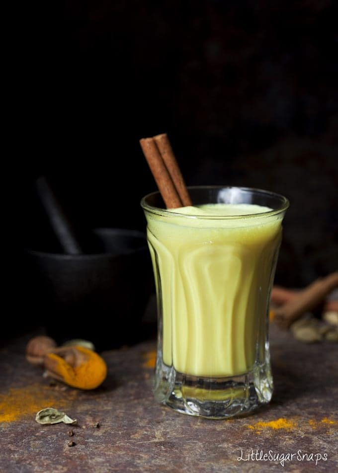A small glass of Golden Milk garnished with a cinnamon stick